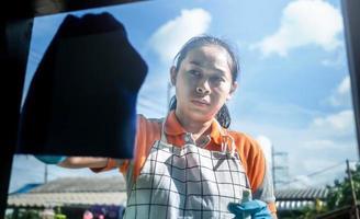 Frau mit Schutzhandschuhen, die das Fenster säubert, indem sie Reinigungsmittel sprüht und mit blauem Lappen abwischt. Reinigungshaus Konzept. foto