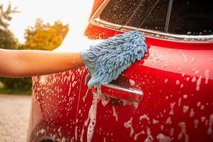 Nahaufnahme von Hand wäscht Auto mit Handschuh mit Seifenblasen im Freien. foto