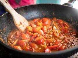berühmtes Essen im Norden Thailands. Hauptbestandteile sind Tomaten und Schweinefleisch. Nahaufnahme von Tomaten in roter Currypaste in der Pfanne. foto