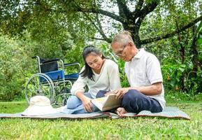glücklicher behinderter Großvater, der sich mit Enkelin im Freien im Park entspannt. Familie glücklicher Lebensstil. foto