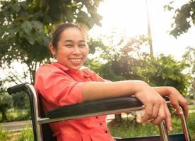 Porträt einer glücklichen positiven behinderten Frau, die im Rollstuhl sitzt und im öffentlichen Park im Freien zur Kamera lächelt foto