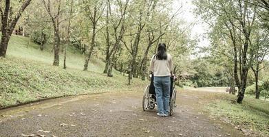 Rückseite des glücklichen Großvaters im Rollstuhl, der sich mit Enkelin im Freien im Park entspannt und spazieren geht. Familie glücklicher Lebensstil. foto