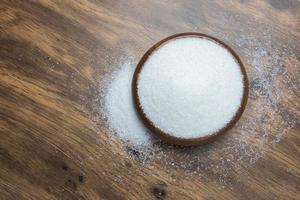 weißer Zucker auf Holzboden foto