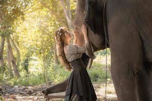 schöne asiatische frau und elefant in der natur foto
