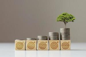 Der Baum wächst aus der Münze, die sich auf dem quadratischen Holzblock befindet, und dem Zielsymbol, dem finanziellen Zielkonzept und dem finanziellen Erfolg. foto