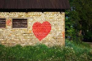 Graffiti malte großes rotes Herz auf gelber Backsteinmauer, umgeben von Gras und Bäumen foto