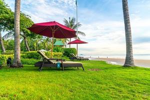Regenschirm mit Stuhl mit Strandhintergrund und Sonnenaufgang am Morgen foto