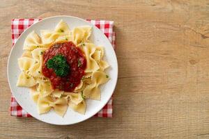 Farfalle-Nudeln in Tomatensauce mit Petersilie - italienische Küche foto
