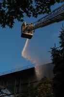 Feuerwehrleute klettern Leiter gegen Bau und Löschen eines Brandes foto