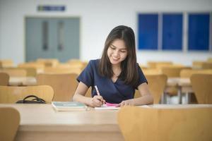 schöne frauen asiatische universitätsstudentin in der bibliothek foto