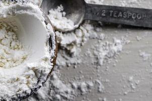 Nahaufnahme einer hölzernen Schüssel Mehl mit einem Teelöffel aus Metall? foto
