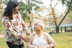 asiatische senior oder ältere alte damenpatientin mit pflege, hilfe und unterstützung auf rollstuhl im park im urlaub, gesundes starkes medizinisches konzept. foto