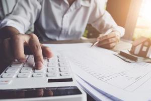 Kunde verwendet Stifte und Taschenrechner, um Hauskaufkredite zu berechnen foto