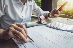 Kunde verwendet Stift, Smartphone und Taschenrechner, um das Hauskaufdarlehen zu berechnen foto