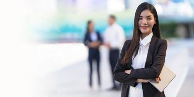 Porträt einer lächelnden Geschäftsfrau, die ein digitales Tablet hält foto