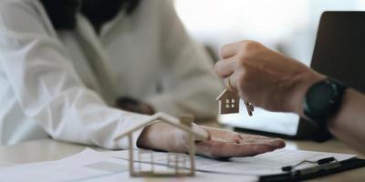 Immobilienmakler, der nach Unterzeichnung der Vertragsvereinbarung im Büro Hausschlüssel für seinen Kunden hält, Konzept für Immobilien, Umzug oder Vermietung von Immobilien foto