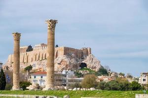 Ruinen des antiken Tempels des Olympischen Zeus in Athen mit dem Akropolis-Hügel im Hintergrund foto