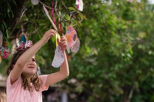 süßes kleines Mädchen hängt am Baum ihre Osterkarten in Eiform, zum Glück und mit guten Wünschen foto