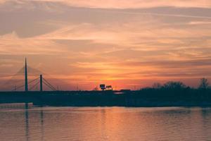 Sonnenuntergang über dem Fluss und der Brücke, Belgrad, Serbien foto