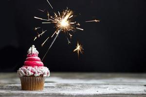 Cupcake mit rotem Strudel-Zuckerguss und Wunderkerze, Weihnachts-Cupcake-Dekoration foto