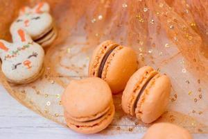 Orangenmakronen mit Schokoladenfüllung und Osterhasenmakronen auf orangefarbenem Tüllhintergrund foto