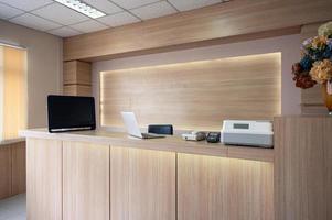 moderner Empfangstresen aus Holz mit Monitor, Laptop und elektronischem Gerät im Krankenhaus foto