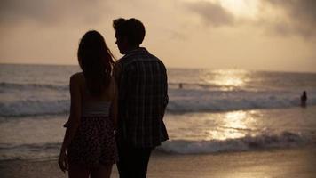 Porträt des jungen Paares Händchen haltend am Strand foto