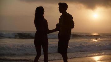 Porträt eines jungen Paares, das am Strand tanzt foto