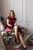 Ein süßes, stilvolles junges Mädchen in einem eleganten burgunderroten Kleid sitzt am Fenster in ihrem Zimmer. Teenager. Abschluss in Schule, College foto