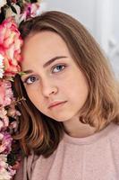 Porträt eines jungen Mädchens an der Wand mit Blumen. foto