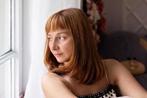 Porträt einer schönen jungen Frau, die am Fenster sitzt. Nahansicht foto