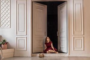 Ein süßes, stilvolles junges Mädchen in einem eleganten burgunderroten Kleid sitzt in der Tür zu ihrem Zimmer. Teenager. Abschluss in Schule, College foto