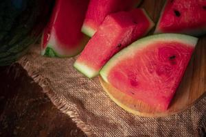 Wassermelone und Wassermelonenstücke in einem Holzhintergrund foto