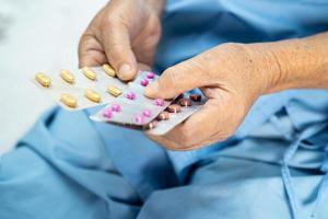 Asiatische ältere oder ältere alte Dame Patientin, die Antibiotika-Kapselpillen in Blisterverpackung zur Behandlung von Infektionspatienten im Krankenhausapotheke-Drogerie-Konzept hält. foto