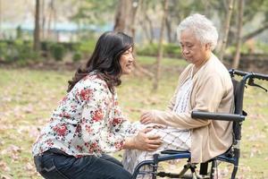 asiatische senior oder ältere alte damenpatientin mit pflege, hilfe und unterstützung glücklich auf rollstuhl im park im urlaub, gesundes starkes medizinisches konzept. foto