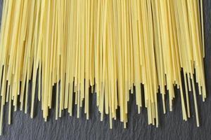 rohe frische Spaghetti, dünn gelb auf schwarzem Hintergrund foto