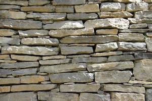 Dekorativer Hintergrund der alten Steinmauer foto