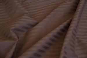 zerknittertes Material mit Falten, Falten auf Stoff, Stoffhintergrund. Bettwäsche. braun mit hellen Streifen, blanko foto