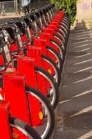 Fahrradverleih auf dem Parkplatz der Stadt mit Sonnenlicht, öffentliches Verkehrskonzept. foto