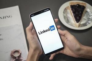 chiang mai, thailand 2019-frau, die ein smartphone mit einer linkedin-anwendung auf dem mobil hält foto