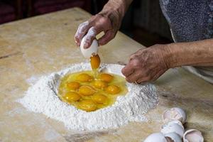 Großmutter bereitet Eier für Teig Teig vor foto