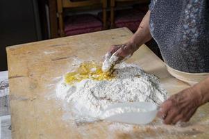 Oma bereitet hausgemachte Pasta zu foto