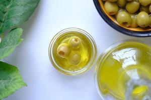 Flasche Olivenöl und frische Oliven in einem Behälter auf weißem Hintergrund foto