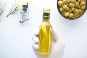 Holding Flasche Olivenöl und frische Oliven in einem Behälter auf Weiß. foto