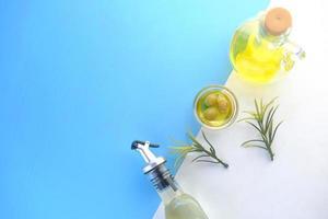 Flasche Olivenöl und frische Oliven in einem Behälter auf farbigem Hintergrund foto
