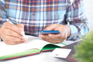 junger Mann Hand mit Smartphone und Schreiben auf Notizblock foto
