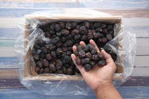 Dattelfrucht von Hand aus einer Schachtel-Draufsicht pflücken foto