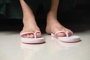Frauenfüße in einem Sendal auf Bodenmatte foto