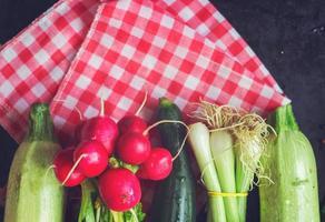 Frühlingsgemüse-Gurke, Frühlingszwiebel, Radieschen, Zucchini auf schwarzem Hintergrund foto