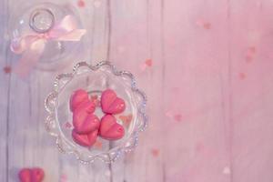 Rosa Schokoladenpralinen in Herzform auf weißem Holzhintergrund mit rosa Kopierraum foto